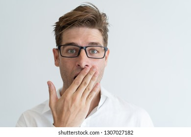 Surprised handsome man covering mouth with hand. Embarrassed young guy wearing glasses and looking at camera. Embarrassment concept. Isolated front view on white background.