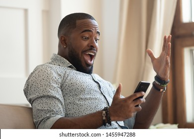 Surprised happy african man holding phone looking at cellphone read good news in sms sit on sofa, amazed black guy winner excited by mobile app win scream with joy celebrate victory success at home