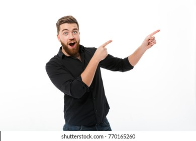 Surprised happy bearded man in shirt pointing away and looking at the camera over white background