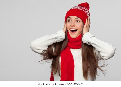 Surprised happy beautiful woman looking sideways in excitement. Christmas girl wearing knitted warm hat and scarf, isolated on gray background