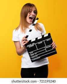 Surprised Happy Beautiful young girl holding a clapperboard on yellow background