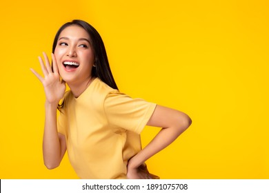 Surprised happy beauty asian woman looking copy space in excitement Expressive facial expressions Presenting some product. Beautiful girl act like a telling secret Isolated on yellow background
