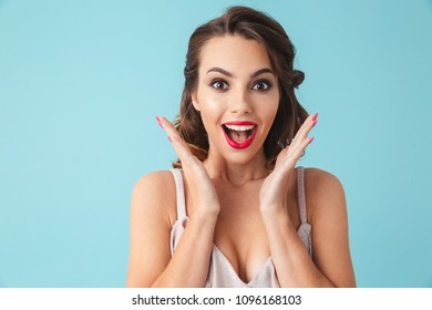 Surprised happy brunette woman in dress rejoices and looking at the camera over turquoise background