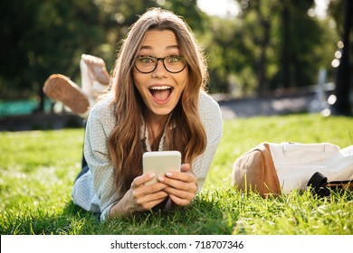 Surprised Happy brunette woman in eyeglasses lying on grass in park with smartphone and looking at the camera