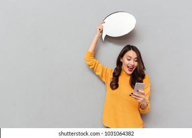 Surprised happy brunette woman in sweater with blank speech bubble overhead using smartphone over gray background