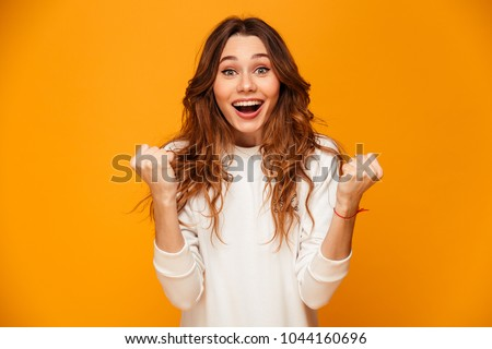 Surprised happy brunette woman in sweater rejoices and looking at the camera over yellow background