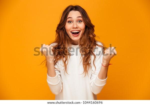 Überraschende glückliche Brunette-Frau in Pulatfreude und Blick auf die Kamera auf gelbem Hintergrund