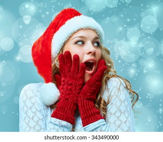 The surprised and happy girl dressed in santa hat. Holiday concept with blue background.