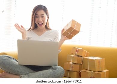 Surprised happy and joyful attractive Asian female entrepreneur with customer many orders list from the website online business in the room and using services parcel fast delivery of shipping company
