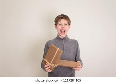 Surprised happy screeming teenager boy opening his present.