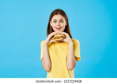 Surprised happy woman holds in her hand a hamburger on a blue background and a yellow T-shirt
