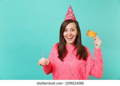 Surprised happy young woman in knitted pink sweater, birthday hat holding in hand cake with candle credit card isolated on blue turquoise wall background. People lifestyle concept. Mock up copy space
