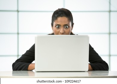 Surprised Indian Business woman working on her laptop.