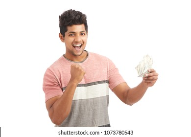 Surprised Indian young man with Indian rupees on white.