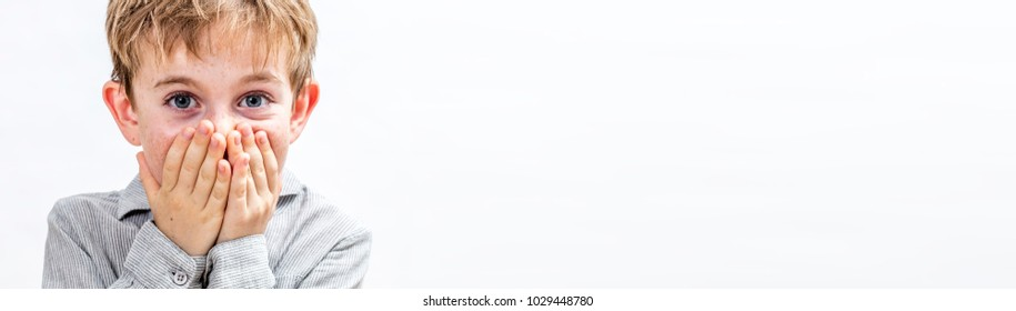 surprised joyful 6-year old boy holding back from bursting out laughing with his hands covering his mouth for shyness or happiness over copy space white background