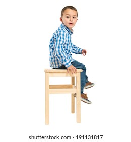 Surprised kid sitting on a wooden chair over white background