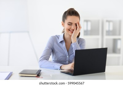 Surprised laughing business woman with laptop in the office background