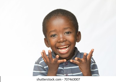 Surprised little African boy excited about getting a present isolated on white