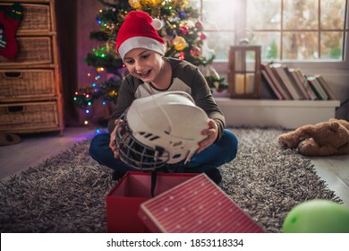 Surprised little boy opening Christmas present.