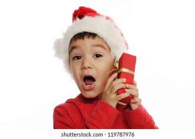 Surprised little boy with Santa hat is holding a small red present