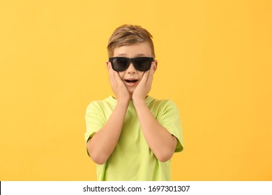 Surprised little boy with sunglasses on color background