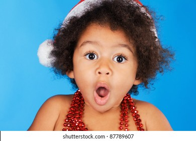 Surprised little child in Christmas hat against blue background