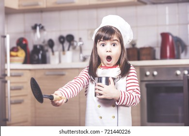 Surprised little girl chef having a funny reaction