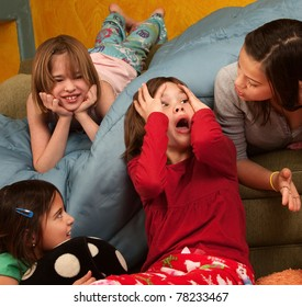 Surprised little girl with hands on head with friends at a sleepover