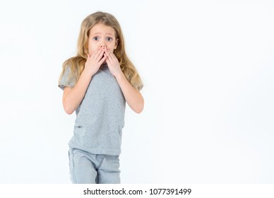 Surprised little girl on a light background. The girl covered her mouth with fright or surprise. Learn the truth.
