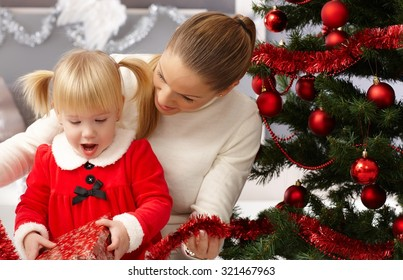 Surprised little girl opening present under christmas tree.