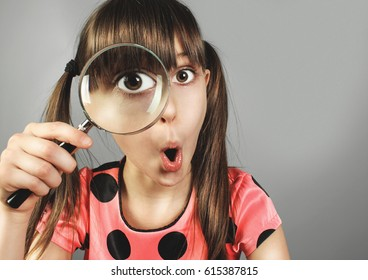 surprised little girl, searching  with magnifying glass