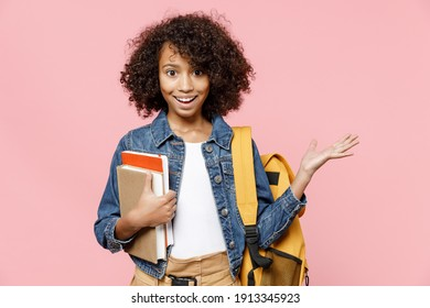 Surprised little smart african american kid school girl 12-13 years old in casual denim clothes backpack hold books spread hands isolated on pastel pink background studio Childhood education concept