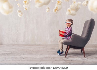 Surprised little spectator with popcorn at home