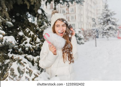 Surprised long-haired female model in white attire having fun in cold snowy day. Outdoor photo of spectacular blonde girl enjoying winter photoshoot with christmas candy.