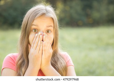 Surprised looking girl with hands over her face over blurred background