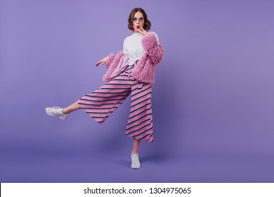 Surprised lovely girl in white shoes posing on purple background during indoor photoshoot. Full-length portrait of interested curly woman in pink pants and elegant fur jacket.