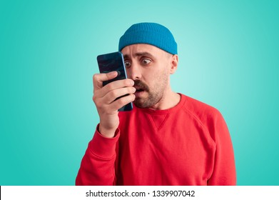 Surprised male hipster in bright blue hat and red sweater staring at smartphone in his hand, isolated on blue background