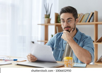 Surprised male office director dressed casually, looks with puzzled expression at payment obligation, studies financial situation, realizes that has complete bankruptancy. Man reads official records