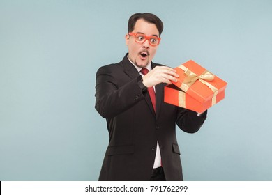 Surprised man in black suit holding red gift box and looking inside with excited face. Studio shot, isolated on light blue background