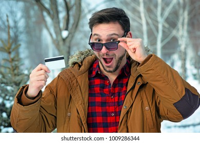 Surprised man in a dark sunglasses looks happy with a credit card in his hand. Funny guy looks like a winner.