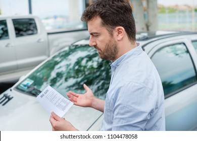 Surprised man finding parking ticket fine on his car