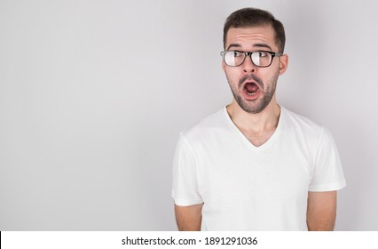 Surprised man with glasses in a white t-shirt looking to the side on a gray background