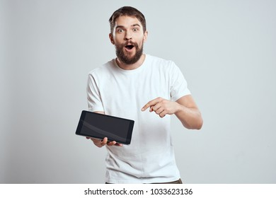 surprised man in a hand holds a tablet on a light background