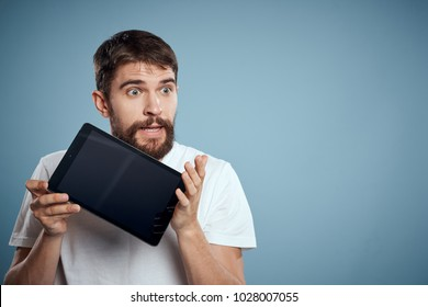 surprised man holding a black tablet looking away on a blue background