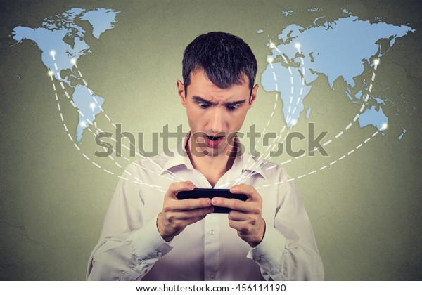 Surprised man holding smartphone connected browsing internet isolated on worldwide world map background.