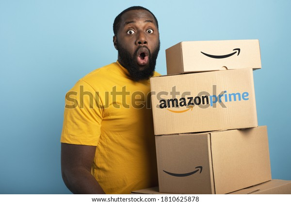 Surprised Man holds a lot of Amazon prime packages. Cyan background