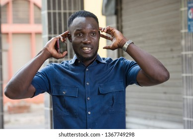 surprised man holds a cell phone in hand holds his ears while listening to a sound outside