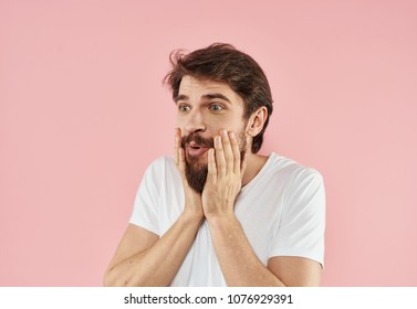 surprised man holds hands on his face, beard, logo
