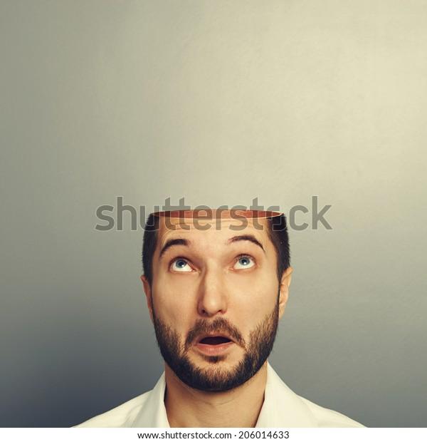 überraschte Mann, der auf seinen offenen leeren Kopf schaute. Foto auf grauem Hintergrund