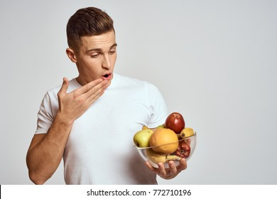 surprised man looks at a plate of fruit on a light background, vitamins, logo